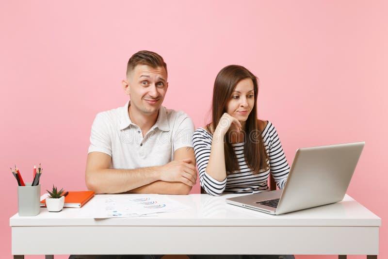 Twee glimlachende bedrijfsvrouwenman collega's zitten het werk bij wit bureau met eigentijdse laptop op pastelkleur roze achtergr royalty-vrije stock foto