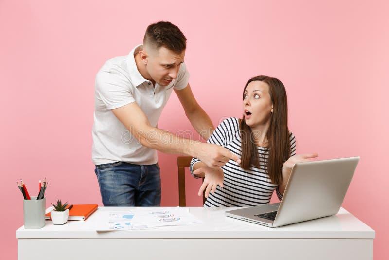 Twee glimlachende bedrijfsvrouwenman collega's zitten het werk bij wit bureau met eigentijdse laptop op pastelkleur roze achtergr royalty-vrije stock foto's