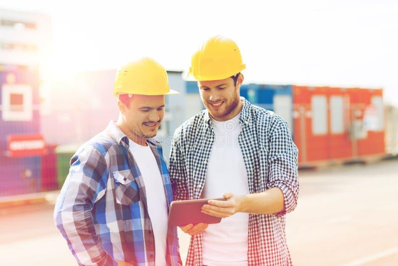 Twee glimlachende bouwers in bouwvakkers met tabletpc royalty-vrije stock afbeeldingen