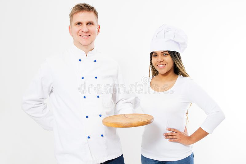 Twee glimlachende chef-koks houden leeg die pizzabureau op witte achtergrond wordt geïsoleerd royalty-vrije stock afbeelding