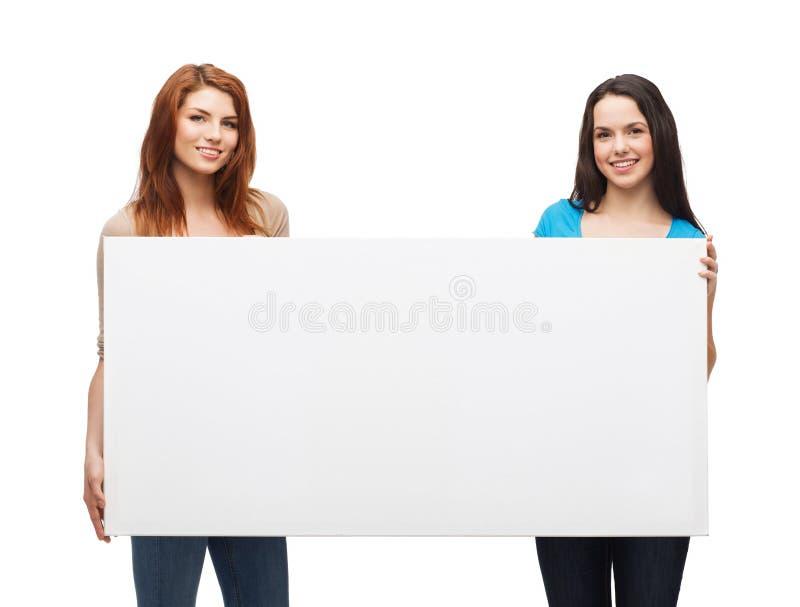 Twee glimlachende jonge meisjes met lege witte raad royalty-vrije stock foto