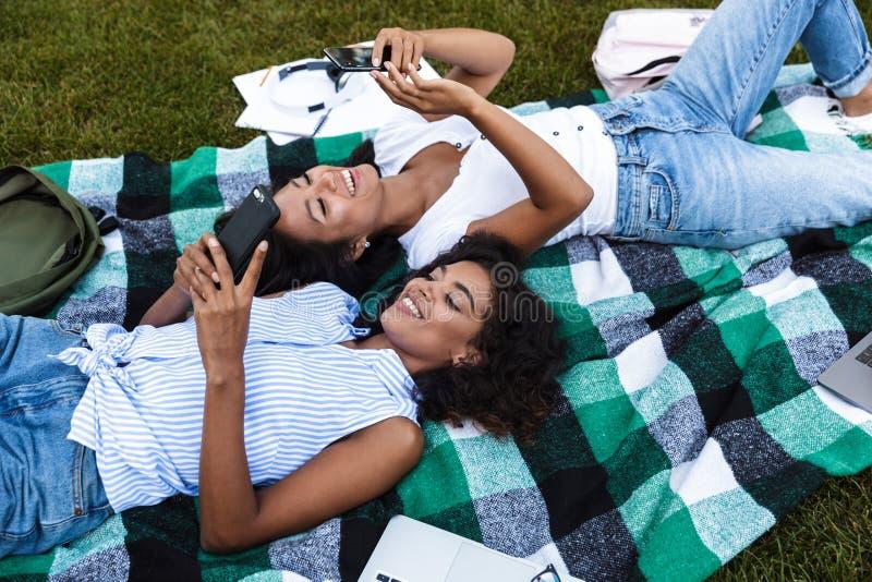 Twee glimlachende jonge studentes die op een gras leggen stock foto