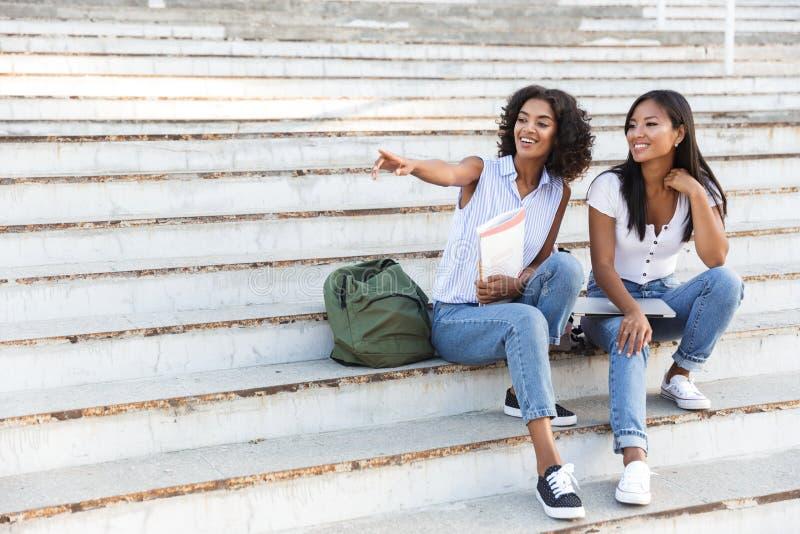 Twee glimlachende jonge studentes die op stappen zitten stock foto