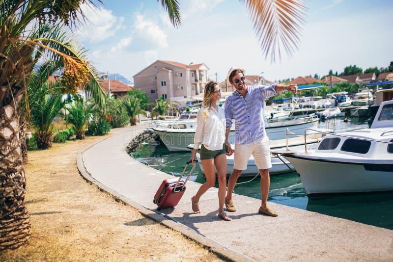 Twee glimlachende jonge toeristen die met koffer lopen stock fotografie