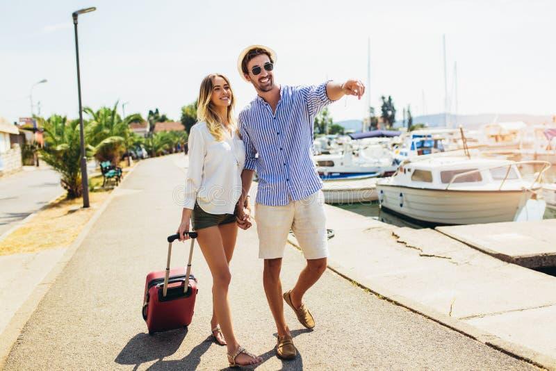 Twee glimlachende jonge toeristen die met koffer lopen royalty-vrije stock foto