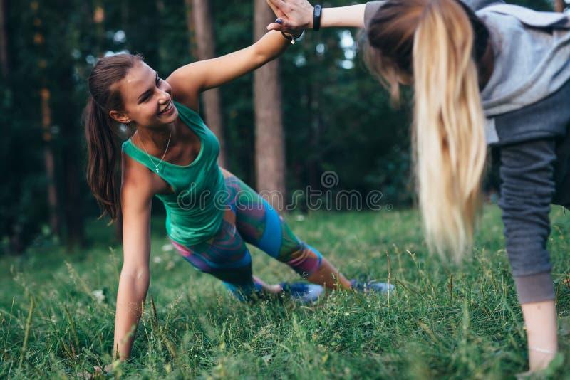 Twee glimlachende jonge vrouwen die op gras in gezondheidskamp uitwerken die zijplank doen die elkaar motiveren die hun handen ho stock fotografie