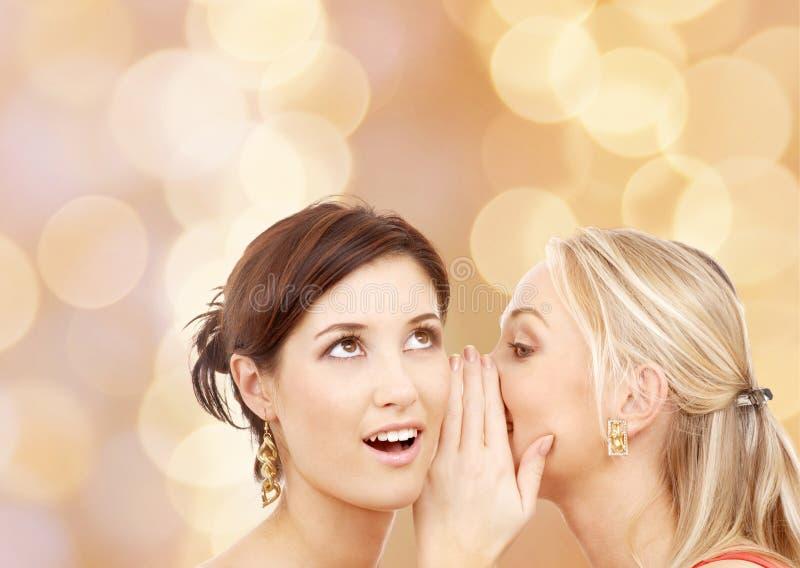 Twee glimlachende jonge vrouwen die roddel fluisteren stock afbeeldingen