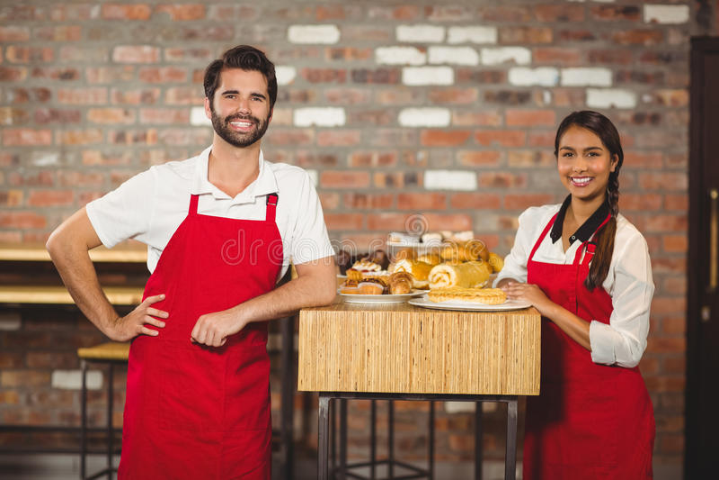 Twee glimlachende kelners die de camera bekijken stock afbeeldingen