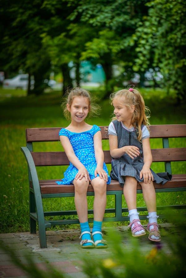 Twee glimlachende kleine zusters zitten op bank stock afbeelding
