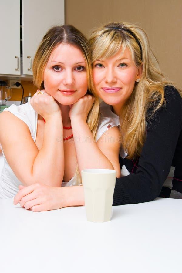 Twee glimlachende meisjes in de keuken stock fotografie