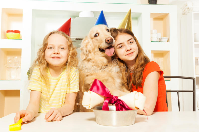 Twee glimlachende meisjes die de verjaardag van het huisdier vieren stock afbeeldingen