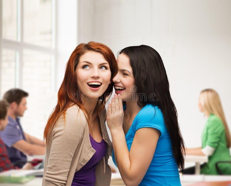 Twee glimlachende meisjes die roddel fluisteren stock foto's