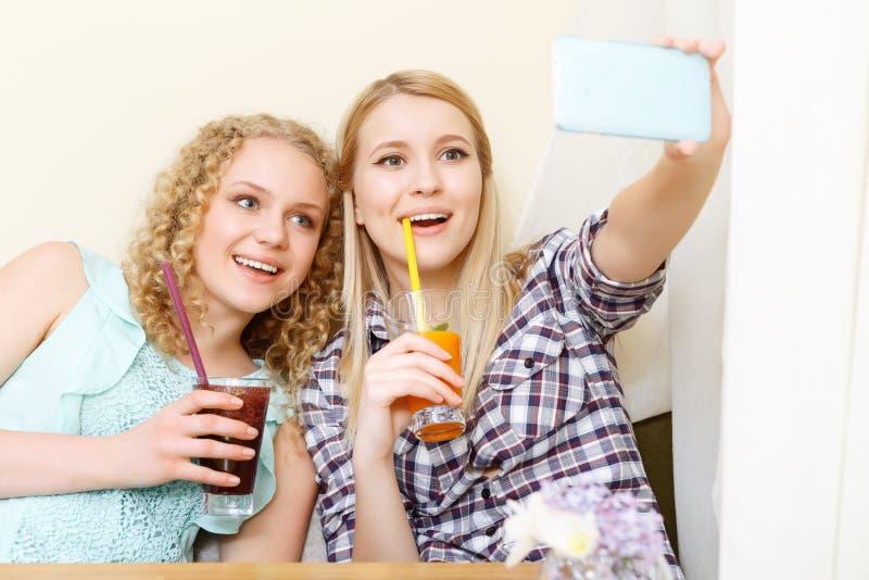 Twee glimlachende meisjes die selfie in koffie doen royalty-vrije stock fotografie