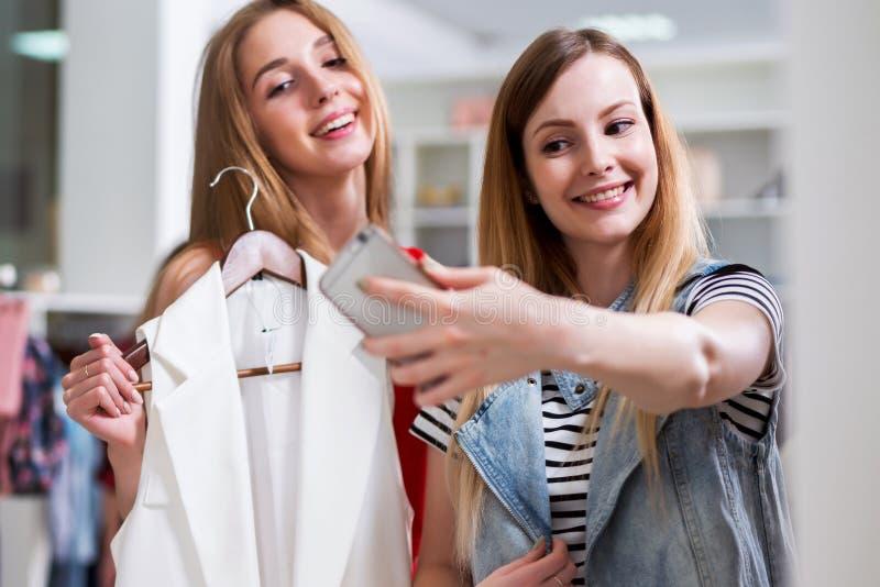 Twee glimlachende meisjes die selfie terwijl het winkelen in een kledingsopslag nemen stock foto