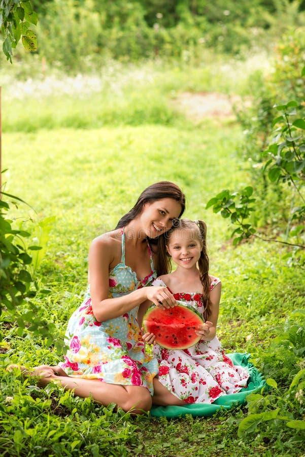 Twee glimlachende meisjes eet plak in openlucht van watermeloen op het landbouwbedrijf royalty-vrije stock afbeeldingen