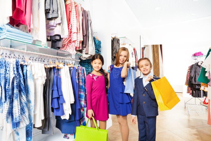Twee glimlachende meisjes en jongen met het winkelen zakken stock fotografie