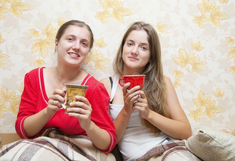 Twee glimlachende meisjes hebben thee stock foto's