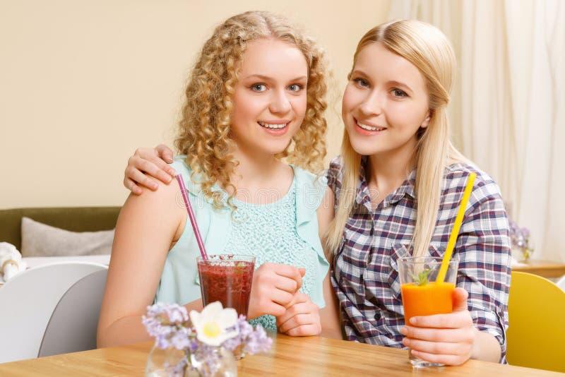 Twee glimlachende meisjes in koffie royalty-vrije stock fotografie