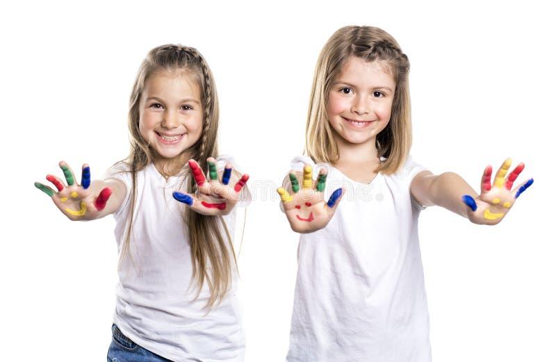 Twee glimlachende meisjes met de palmen schilderden door een verf Geïsoleerdj op witte achtergrond royalty-vrije stock foto's