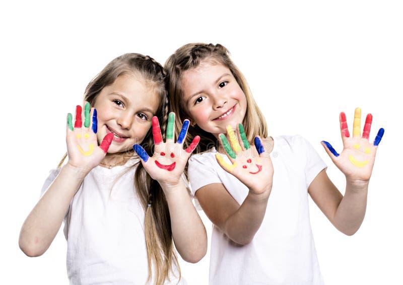Twee glimlachende meisjes met de palmen schilderden door een verf Geïsoleerdj op witte achtergrond stock afbeeldingen