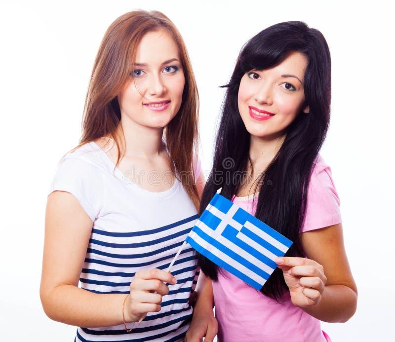 Twee glimlachende meisjes met Griekse vlag. royalty-vrije stock afbeeldingen