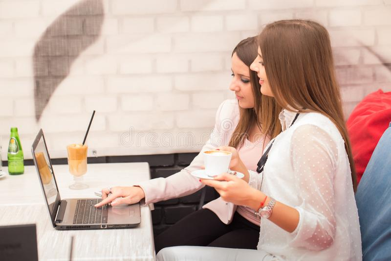 Twee glimlachende onderneemsters die nieuw project op laptop bespreken royalty-vrije stock afbeelding