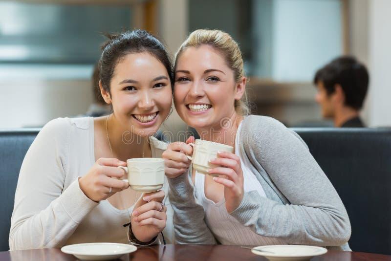 Twee glimlachende studenten in de winkel van de universiteitskoffie stock afbeeldingen
