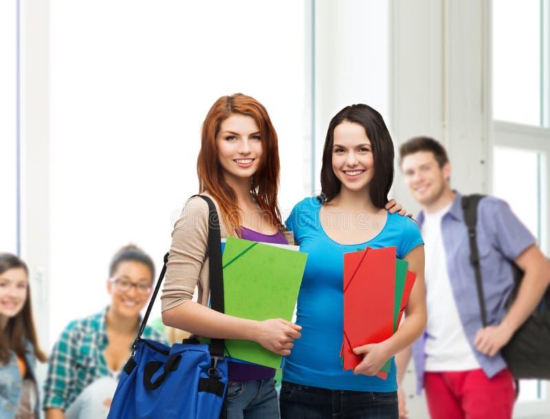 Twee glimlachende studenten met zak en omslagen royalty-vrije stock afbeelding