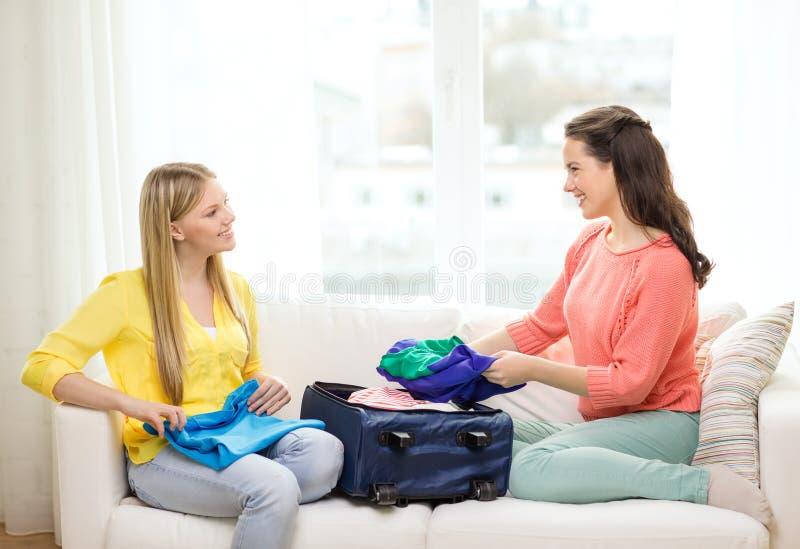 Twee glimlachende tieners die koffer thuis inpakken stock foto's