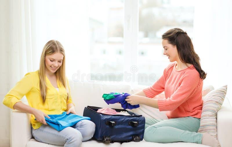 Twee glimlachende tieners die koffer thuis inpakken royalty-vrije stock afbeeldingen
