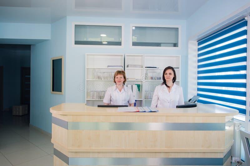 Twee glimlachende verpleegsters die bij het bureau van de het ziekenhuisontvangst werken stock foto's
