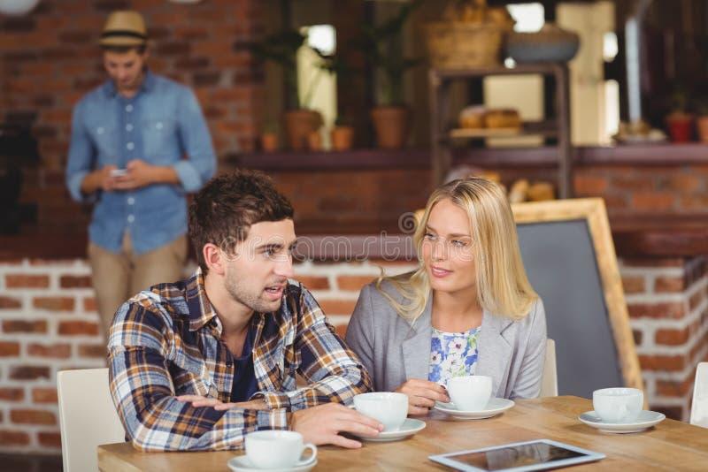 Twee glimlachende vrienden die en koffie spreken drinken stock fotografie