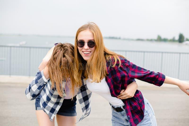 Twee glimlachende vrouwelijke vrienden die elkaar op de straat koesteren Vakantie, vakantie, liefde en vriendschapsconcept royalty-vrije stock foto