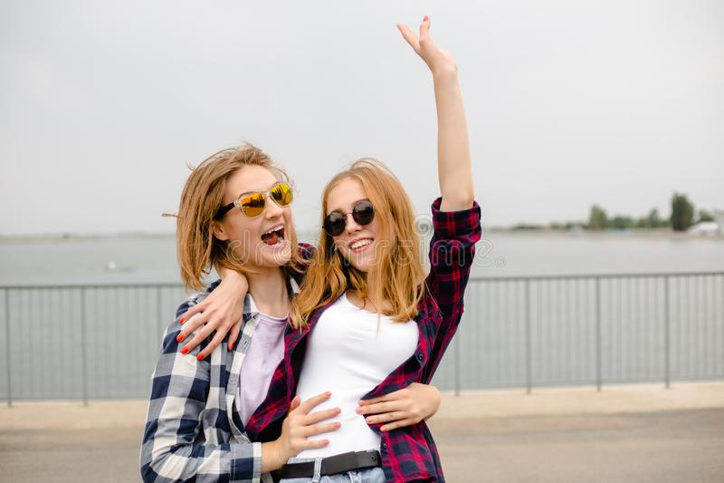 Twee glimlachende vrouwelijke vrienden die elkaar op de straat koesteren Vakantie, vakantie, liefde en vriendschapsconcept royalty-vrije stock fotografie
