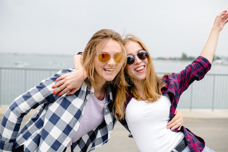 Twee glimlachende vrouwelijke vrienden die elkaar op de straat koesteren Vakantie, vakantie, liefde en vriendschapsconcept stock foto