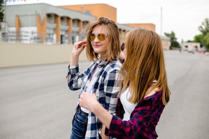 Twee glimlachende vrouwelijke vrienden die elkaar op de straat koesteren Vakantie, vakantie, liefde en vriendschapsconcept stock afbeelding