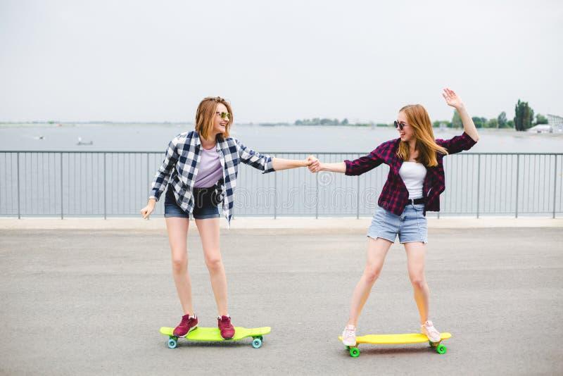 Twee glimlachende vrouwelijke vrienden die het berijden longboard met het helpen van elkaar leren Het concept van de vriendschap royalty-vrije stock foto