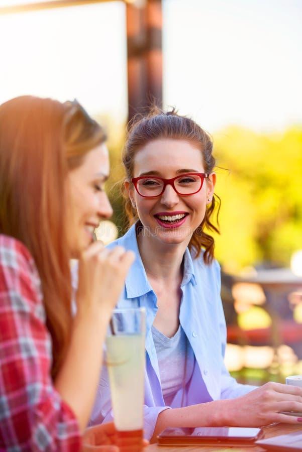 Twee glimlachende vrouwelijke vrienden die, het drinken koffie in openlucht in de stad spreken royalty-vrije stock foto