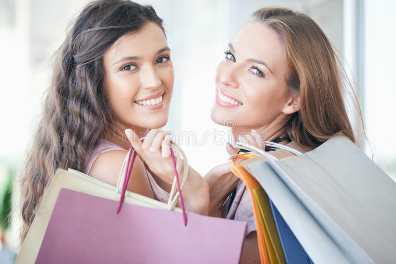 Twee glimlachende Vrouwen die samen winkelen stock afbeeldingen