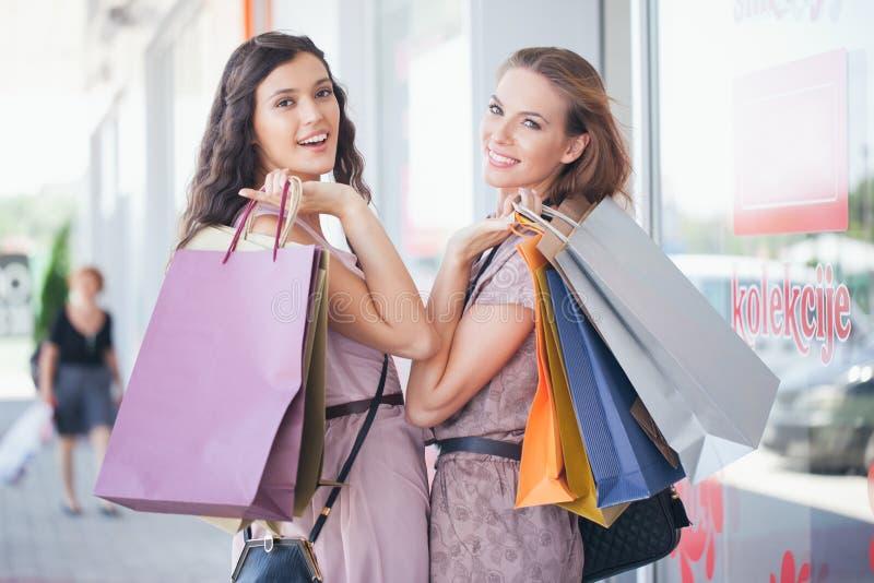 Twee glimlachende Vrouwen die samen winkelen royalty-vrije stock afbeelding