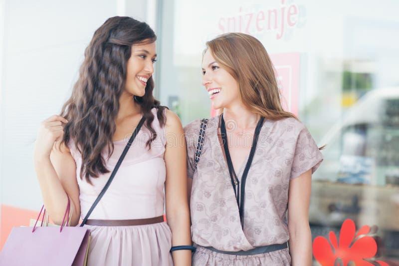 Twee glimlachende Vrouwen die samen winkelen stock foto