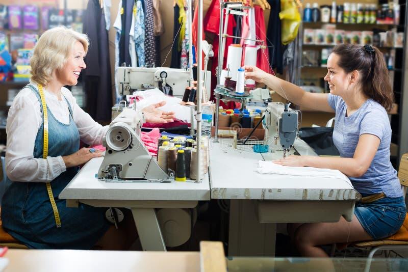 Twee glimlachende vrouwenkleermakers die met naaimachines werken stock afbeeldingen