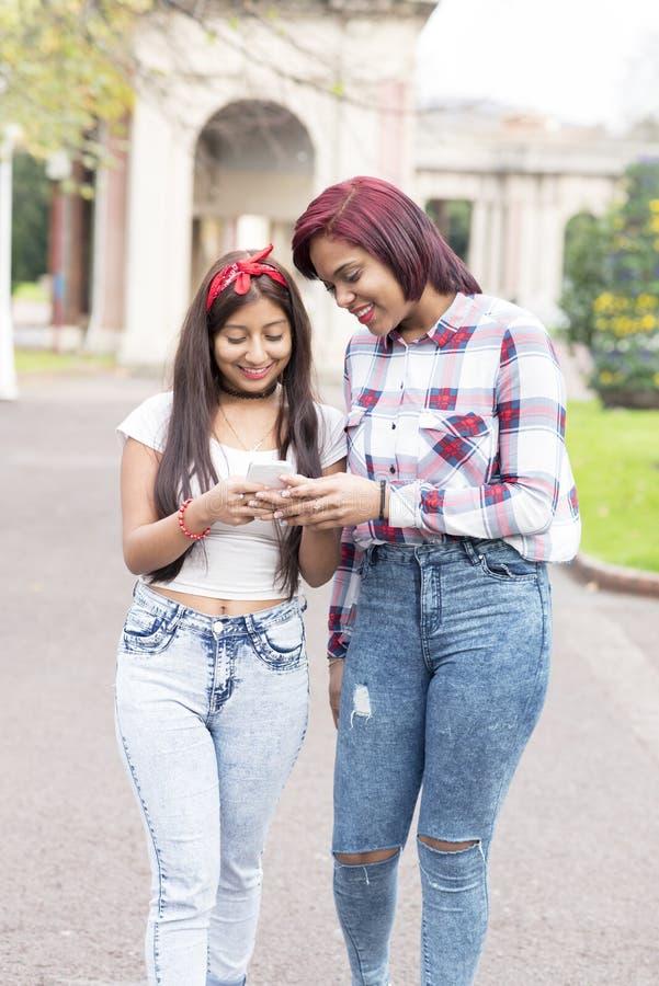 Twee glimlachende vrouwenvrienden die slimme telefoon met behulp van stock fotografie