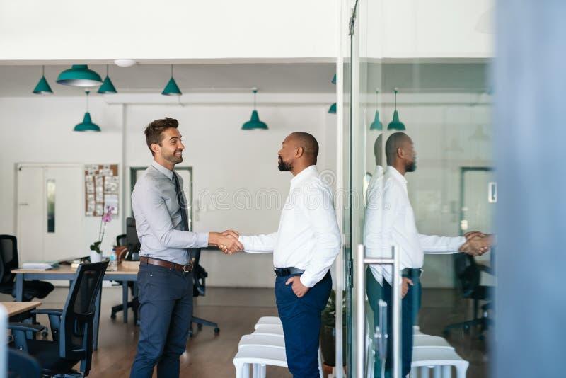 Twee glimlachende zakenlieden die handen samen na een bureauvergadering schudden royalty-vrije stock afbeeldingen