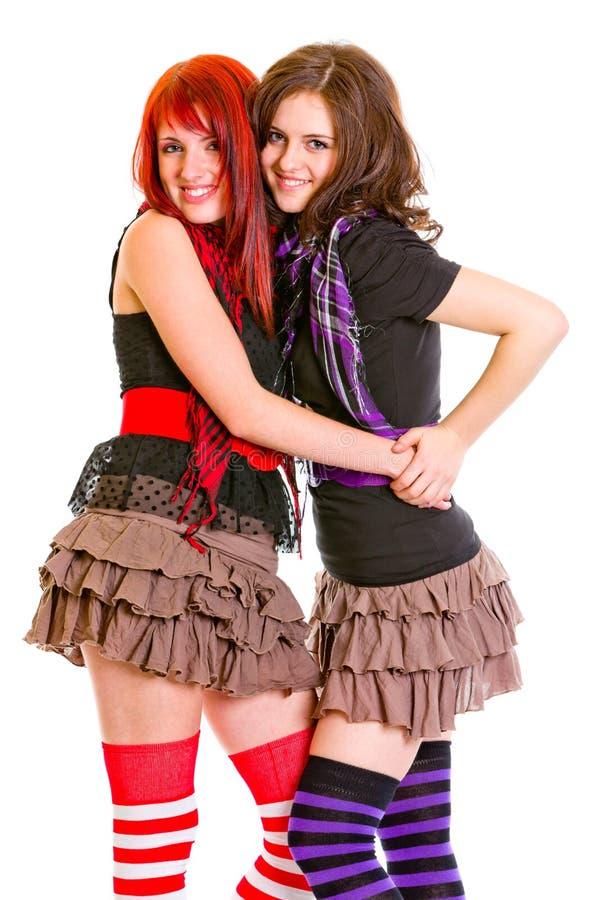 Twee goede meisjes die gelukkig omhelzen stock afbeeldingen