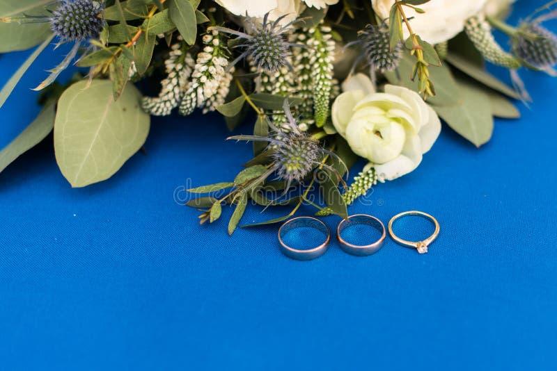 Twee gouden bruiloftringen en verlovingsring met een diamant op blauwe achtergrond royalty-vrije stock foto