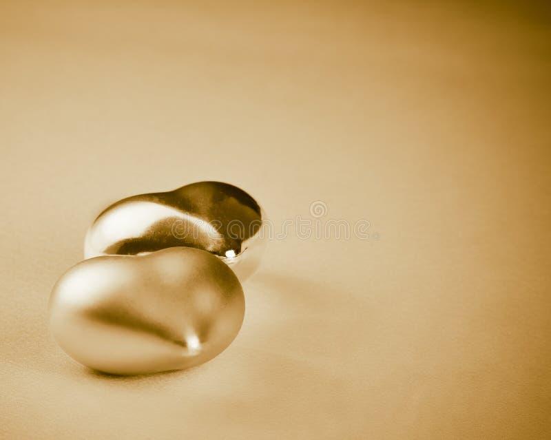 Twee gouden die harten op gouden achtergrond, concept worden geïsoleerd valentijnskaartdag royalty-vrije stock fotografie