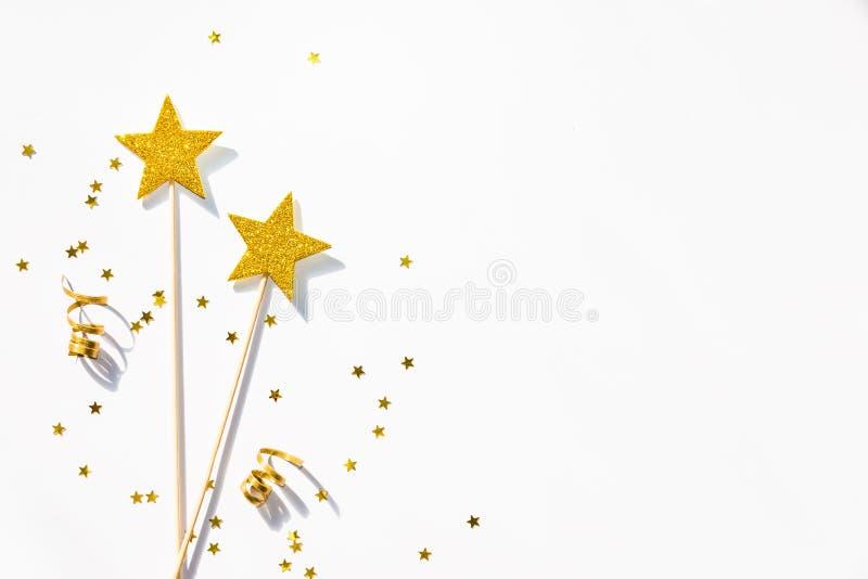 Twee gouden partijtoverstokjes, lovertjes en linten op een witte achtergrond De ruimte van het exemplaar royalty-vrije stock afbeelding