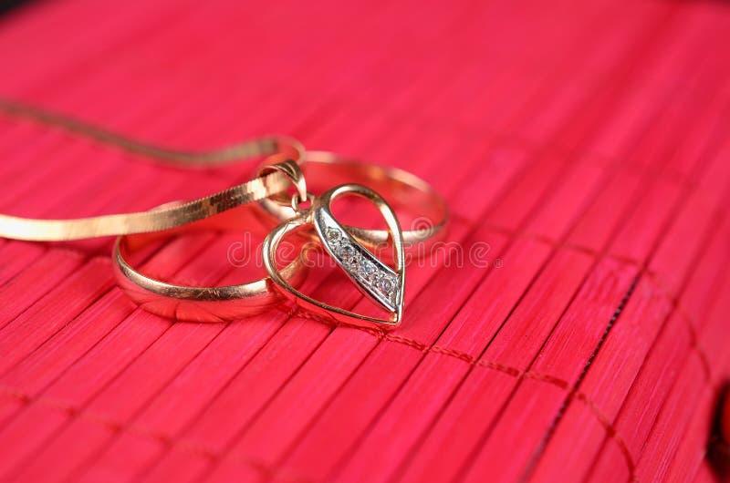 Twee gouden trouwringen en gouden hart royalty-vrije stock foto's