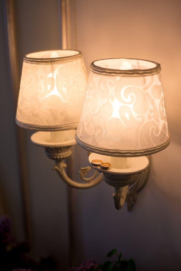 Twee gouden trouwringen en mooie lamp royalty-vrije stock fotografie